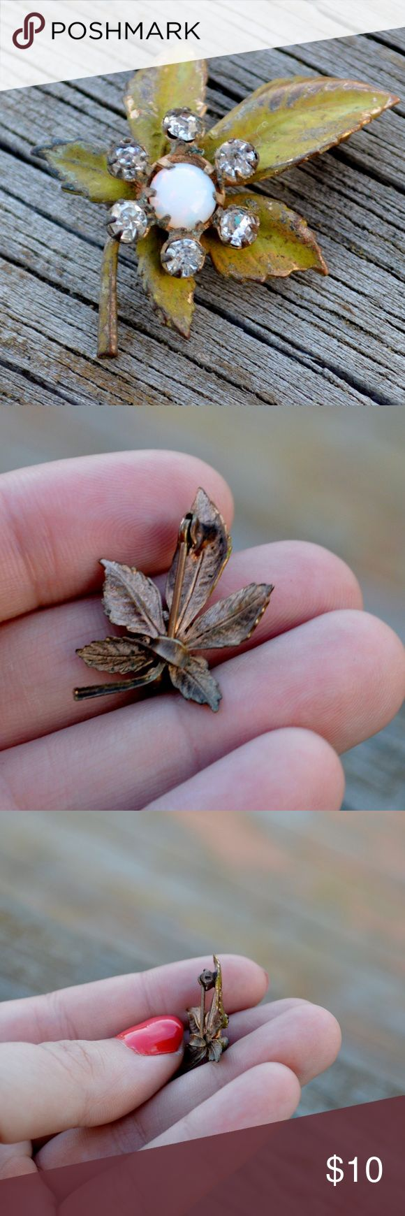 Antique CZ Rhinestone Leaf Faux Fire Opal Pin Up for sale is one pin, as pictured. It is a very old (maybe 1920s) leaf pin. It features a coppery/goldish toned metal with green enamel paint, rhinestones and what I believe is a faux opal (a bit of fire at the right angles). It measures about 1.15  inches tall by about .8 inches wide. It has age wear (should be noticeable via pictures, pretty heavy from age, but the pin is still totally wearable). It features a non-locking c-clasp that is not…