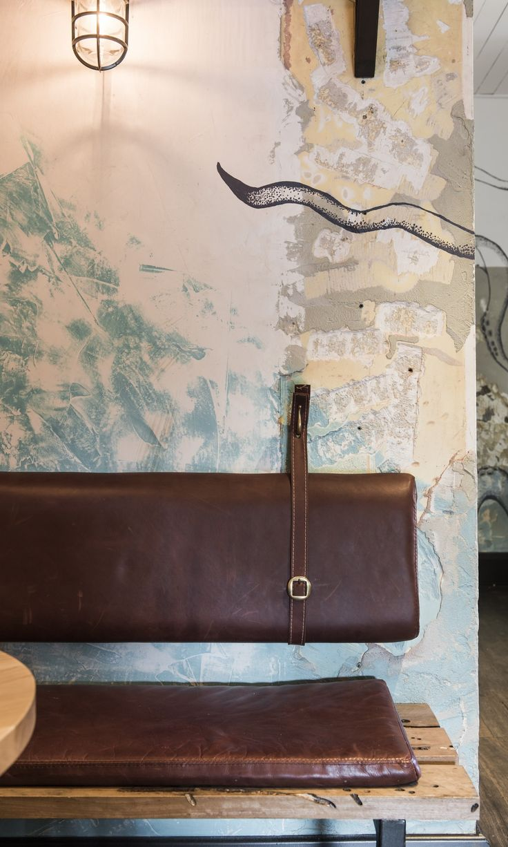 Inspiration for a DIY headboard. Wrap leather / fabric around a piece and then hang with leather / belts / similar on hooks. (Archello?)