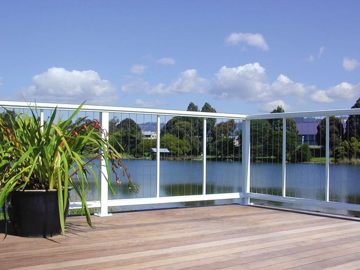 Aluminum railings with vertical cable infill on coastal deck:DesignRail® aluminum railing with vertical CableRail infill option.