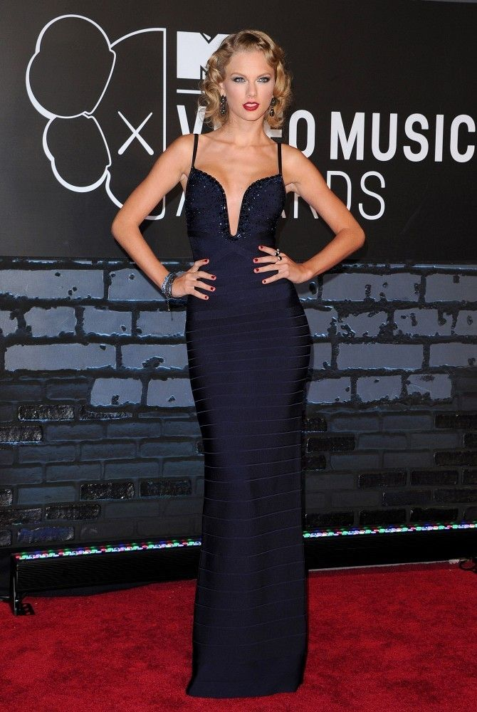 Taylor Swift showed off her curves with this midnight blue bandage dress with a deep plunging neck. Brand: Herve Leger by Max Azria