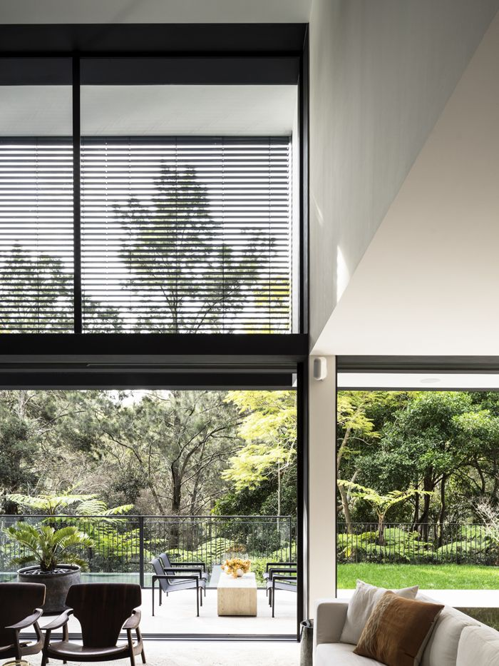 Tobias Partners - Cooper Park House. Double-height windows. Around a custom-made stone table outside are Knoll '1966 Lounge Chairs' by Richard Schultz from De De Ce. Terrace is in 'Roma' travertine from Artedomus.