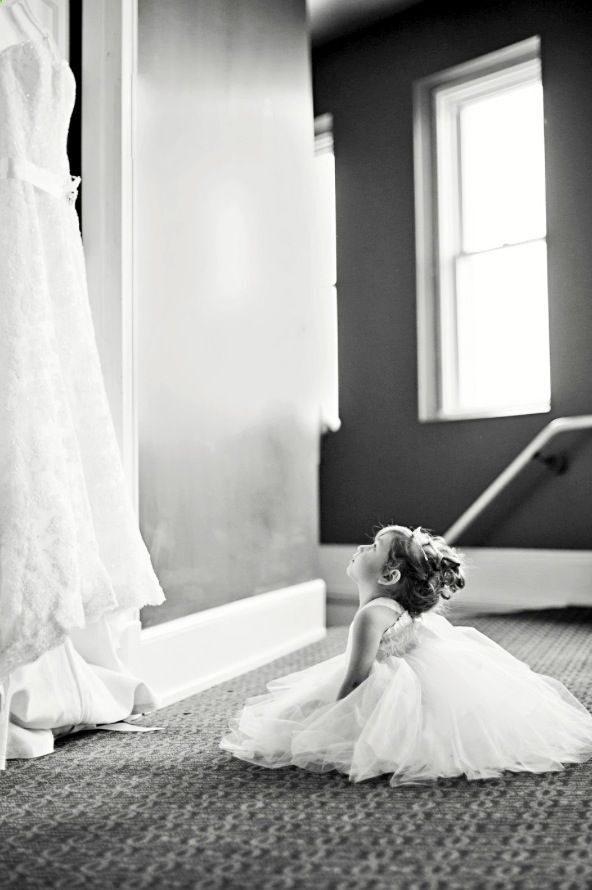 Flower girl looking at wedding dress.