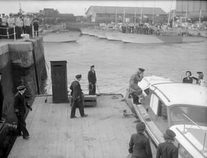 E-BOATS AND E-BOAT ADMIRAL SURRENDER. 13 MAY 1945, HMS BEEHIVE, FELIXSTOWE. 2 GERMAN E-BOATS, THE FIRST SURFACE CRAFT TO SURRENDER, WERE ESCORTED IN BY 10 BRITISH MTB'S. ON BOARD ONE OF THE E-BOATS WAS REAR ADMIRAL KARL BRUNING, WHO HAD BEEN IN CHARGE OF E-BOAT OPERATIONS AND WHO SIGNED THE INSTRUMENT OF SURRENDER.
