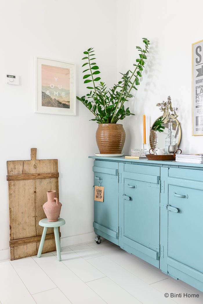 Bright popping blue cabinets, white walls, wooden accents, large plant branches