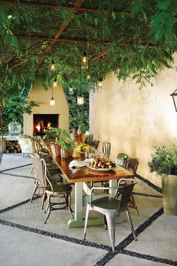 Humble materials can pull off a high-end look. This backyard transformation began by installing a 10-foot-wide by 30-foot-long iron pergola. Then, wisteria was planted, which in time turned into a leafy canopy overhead. To anchor the space, an outdoor fireplace was constructed from cinder blocks lined with fireproof brick and covered in stucco.     See more of this Canopy Patio