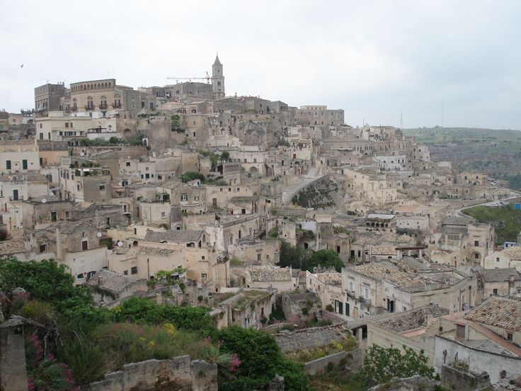 "Matera has gained international fame for its ancient town, the ""Sassi di Matera"". The Sassi originate from a prehistoric (troglodyte) settlement, are suspected to be some of the first human settlements in Italy"