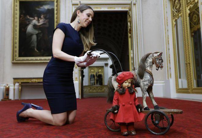 Le cheval sur roulettes qui est ici présenté par une employée de Buckingham Palace a accueilli sur sa selle l'actuelle reine d'Angleterre Elizabeth II ainsi que sa sœur, Margaret. À ses côtés se tient de nouveau «Pamela», la poupée chaperon rouge.
