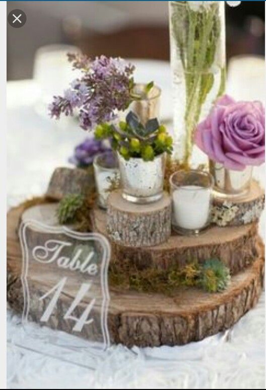Love the stacked wood slabs layered with flowers and a calligraphy number - perfect centerpiece for any occasion!