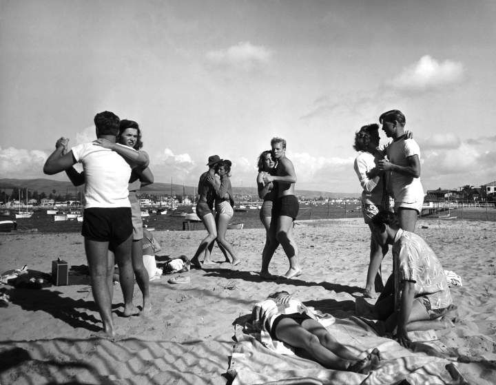 <b>Caption from LIFE.</b> Dancing by day to music of a portable radio, students shuffle through the soft footing. Most of them stayed at Balboa Beach for four or five days.