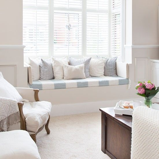 This charming neutral living room is given a soft nautical edge thanks to the window seat… Pale blue and white striped upholstry adds a coastal feeling to the room without it overwhelming it… See more of this stunning home!