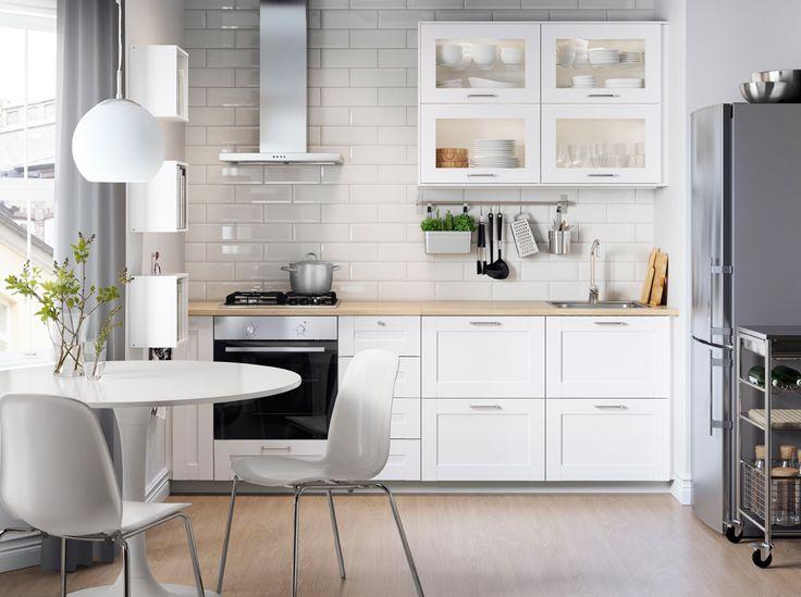 Cocina blanca con electrodomésticos en acero inoxidable, sillas blancas y mesa redonda.