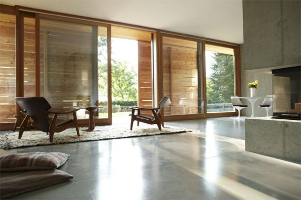 Love the warm-colored concrete and the warm, rounded edges of the wood in this modern place.