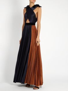 Roksanda Mehtroa pleated silk-blend satin gown Roksanda Illincic's ankle-grazing silhouettes have a sensuous feel for AW16. This midnight-blue Mehtroa gown crosses over at the front to show a hint of skin, and falls into a sunray-pleated skirt for beautiful movement. A contrasting sepia-brown side panel and rich black velvet trims bring a signature artistic twist. Style it simply with sky-high sandals for autumnal occasions.