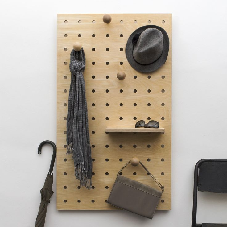 Handcrafted Scandinavian style plywood pegboard as hallway coat rack and storage