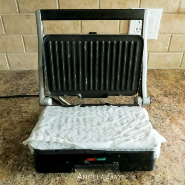 Een panini grill maak je schoon door er wat vochtig keukenpapier met azijn op te leggen. Even warm laten worden stomen. Daarna kan je de grill zo schoonvegen.