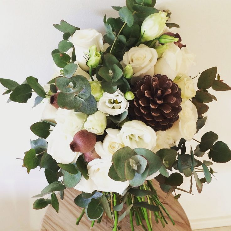 Rustic bouquet of roses, lisianthus, eucalyptus, gum nuts and pine cones
