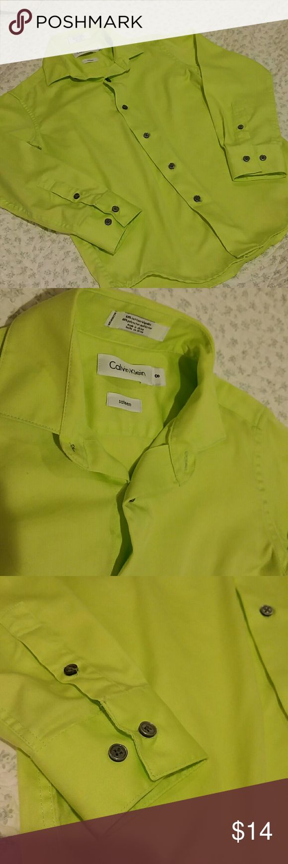 CALVIN KLEIN NEON GREEN DRESS SHIRT SZ.8 If your little guy likes to stand out in a crowd and this Calvin Klein button-up dress shirt is him it's in a neon green lime color in a sentence in Spanish buttons at the sleeve and buttons down the center previously owned but in excellent condition Calvin Klein Shirts & Tops Button Down Shirts
