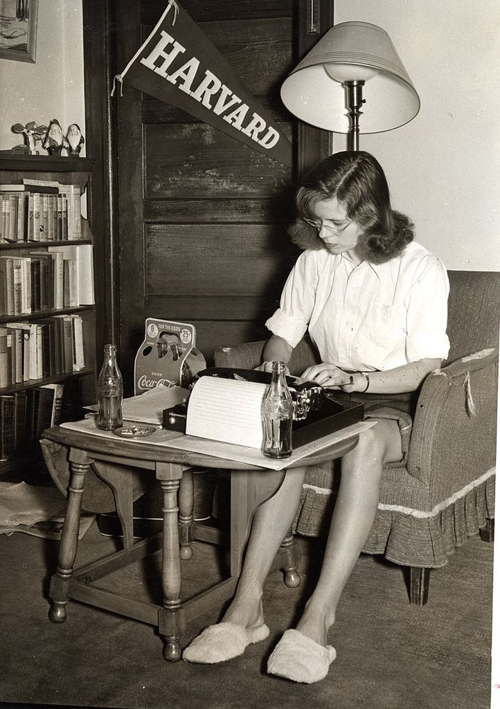 "Among books and notes, a Vassar student studies at her typewriter in her dorm room, 1950's. © Vassar College, Archives & Special Collections. ""College is a place to keep warm between high school and an early marriage."" — George Gobel."