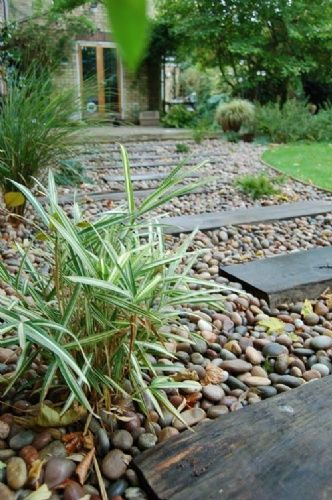 garden path tumbled pebbles with inset timber sleepers