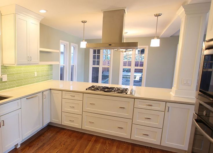 kitchen peninsula with cooktop, stainless range hood and ...