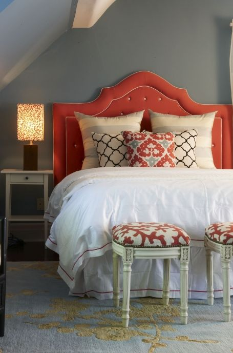 Love! Beautiful coral - gray - yellow bedroom design: Slate paint color on wall, coral red tufted headboard with white piping, white bedding with red stitching, cream and yellow rug, white & black moorish tile pillows, ivory & gray silk striped pillows and ivory french stools with red coral linen upholstery.