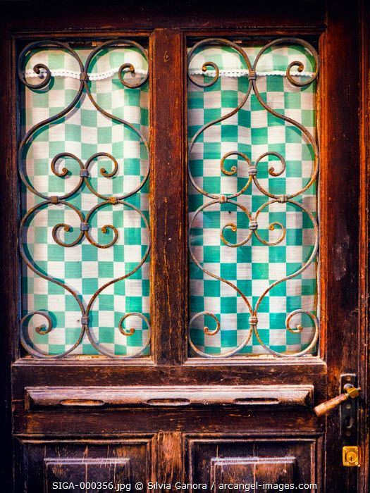 Old windowed door detail with checkered tent and ornate grate - ©Silvia Ganora Photography - All Rights Reserved  #bookcovers #doors