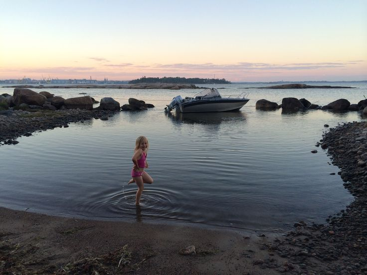 Child guest swimming at the summer cottage. And the boat in the background.