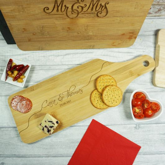 Couples Bamboo Paddle Board.  Treat any couple to this beautifully personalised bamboo paddle cheeseboard. With a delicate script font, it's a brilliant gift for weddings, anniversaries or just because!    Personalise this bamboo cheese board with the happy couples name and a special date to mark the start of their adventure together.