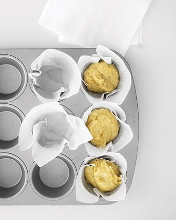 1. Cut 5-inch square pieces of parchment.     2. Spray a muffin tin with vegetable oil cooking spray to hold parchment in place.     3. Place 1 piece of parchment into 1 cup of the tin, pressing along folds to crease. Repeat with other cups and parchment pieces.     4. Scoop batter into cups, and bake.