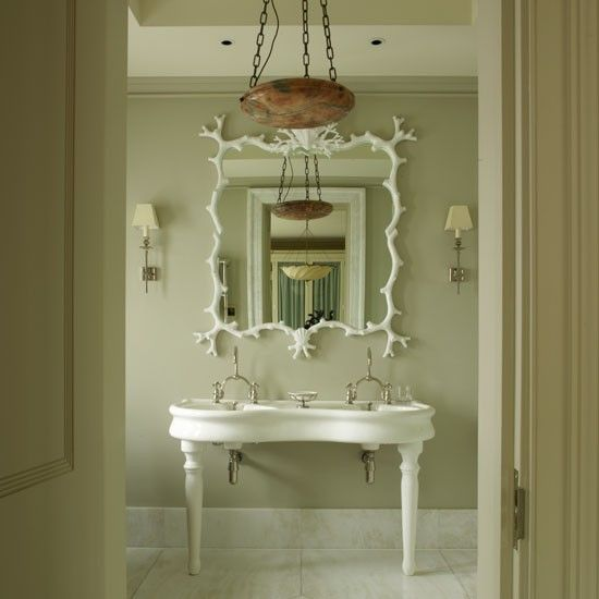 A French-style console basin with a decorative mirror.