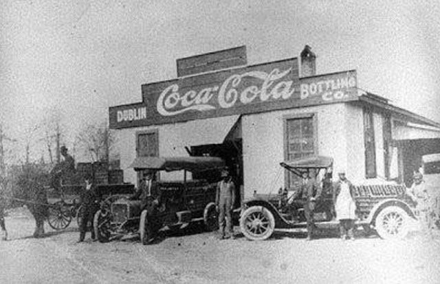 Coca Cola in Dublin, GA, 1912. Everybody is prepared for the camera shot. Men working together around Dublin's first Coca Cola plant. Stock is showcased in conveyance vehicles. They might be glad for the cases in the trucks, however they would have no clue how far of an overall achieve Coca Cola would in the end have. vintage everyday: 25 Amazing Early Photos of the World's Most Iconic Companies