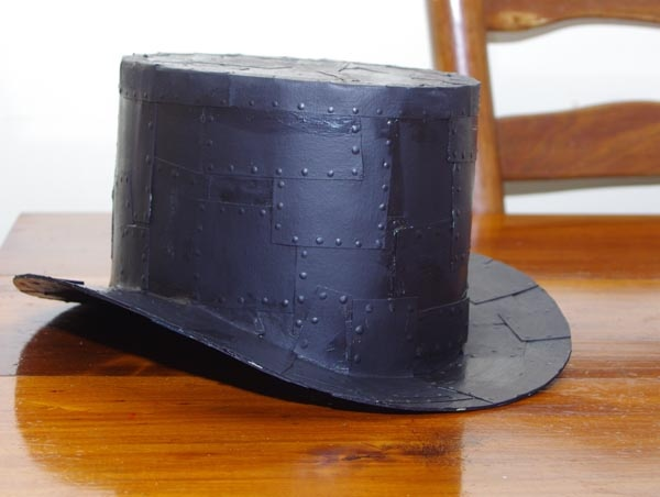 Top hat from cardboard :) Totally made this turned out completely awesome. One thing to add...I would suggest making a strip of cardboard to fit around your head and fasten with a brass brad  so you can custom fit the hat it also gives you a pattern for making the brim and top. Also we did not use epoxy stuff we punched holes out of styrofoam plate and glued each one on with hot glue gun took about an hour but it turned out awesome.