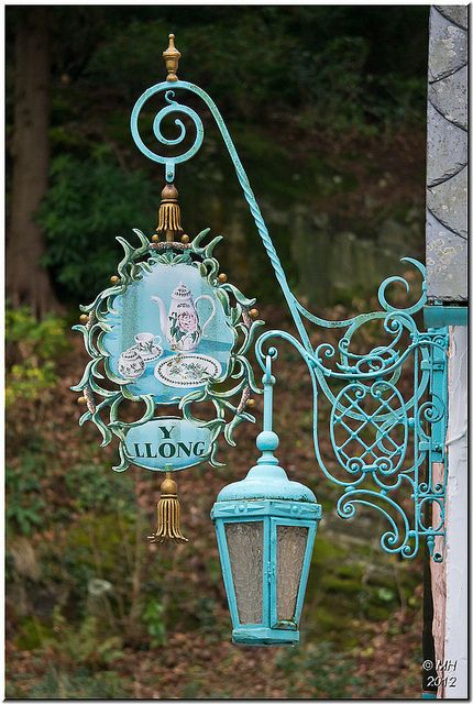 Portmeirion  popular tourist village in Gwynedd, North Wales, GB    The shop signs and lamps are an iconic part of Portmeirion - especially in this trademark shade of turquoise, used throughout the village. The sign above shows the famous Portmeirion pottery.