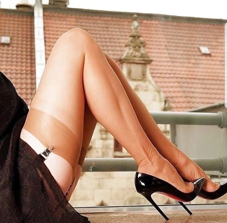 Sexy girl putting her red high heels shoes on stock photo