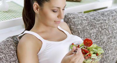 Schwangere auf dem Sofa mit einem Salat auf dem Bauch
