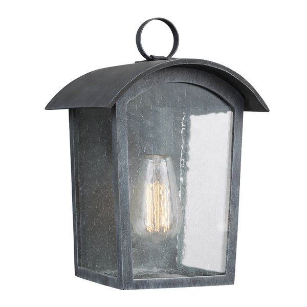 Be welcomed home with a warm glow and charming style when you hang this outdoor flush mount to your home. Taking inspiration for cottage-chic designs, it showcases a clean-lined base frame with a rounded top and a ring handle. Set in the frame are three clear seeded glass panels that diffuse the light within. The ash black finish adds vintaged appeal to the look, and it features space for a 60-watt bulb (not included).