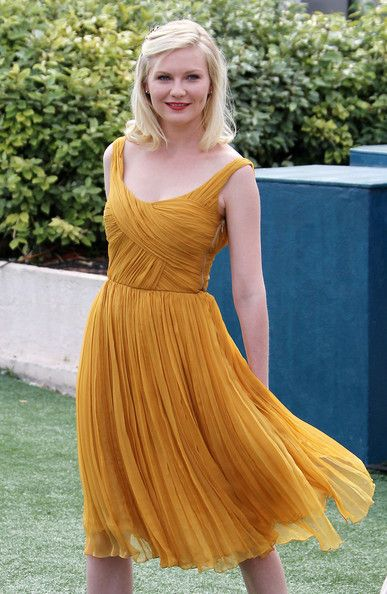 Kirsten Dunst in a mustard colored dress at the  Melancholia photocall at the 64th Cannes Film Festiva.