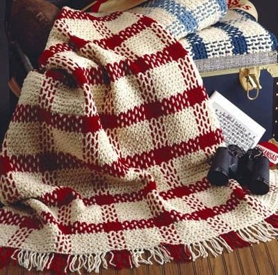 """Comfy Plaids Blanket - Create this patterned blanket in a double crochet mesh with two strands of yarn woven through to form the plaid; one main color with one contrasting color are used throughout the pattern.The ends are knotted to form the fringeThe approximate finished size is: 46"""" x 58"""