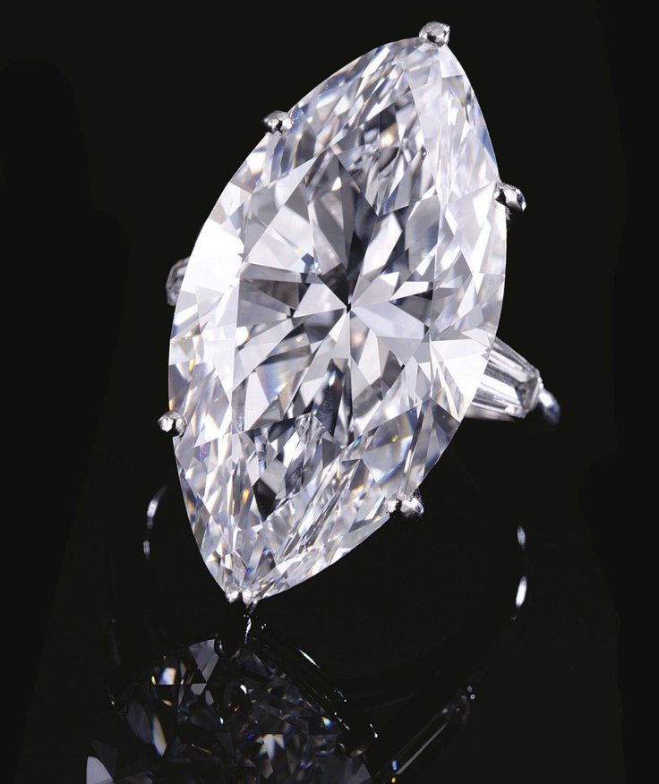 IMPORTANT DIAMOND RING, CARTIER.  Set with a marquise-shaped diamond weighing 22.25 carats, between tapered baguette diamond shoulders, mounted in platinum,  signed Cartier Paris, French assay and maker's marks.  size 52,