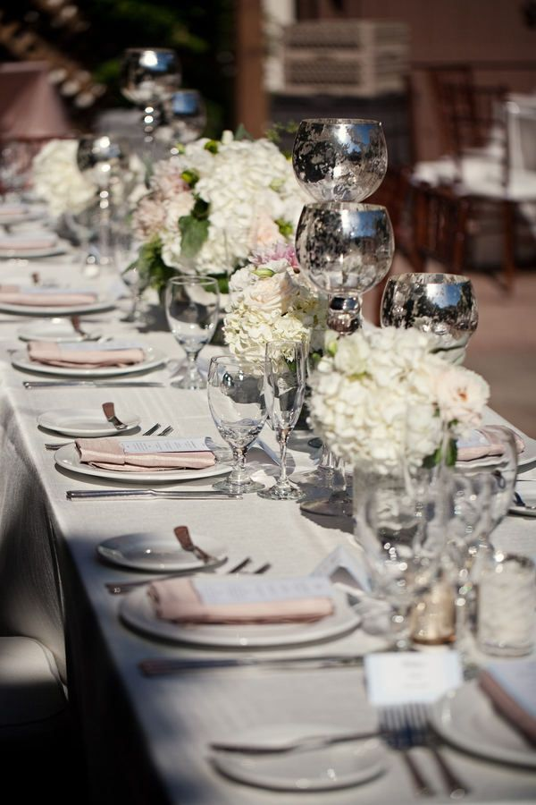 Elegant tablescape with mercury glass candle holders, white and pink flowers and neutral linens.