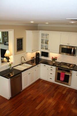 White subway tile, white cabinets, black countertop, dark wood floor, stainless steel appliances