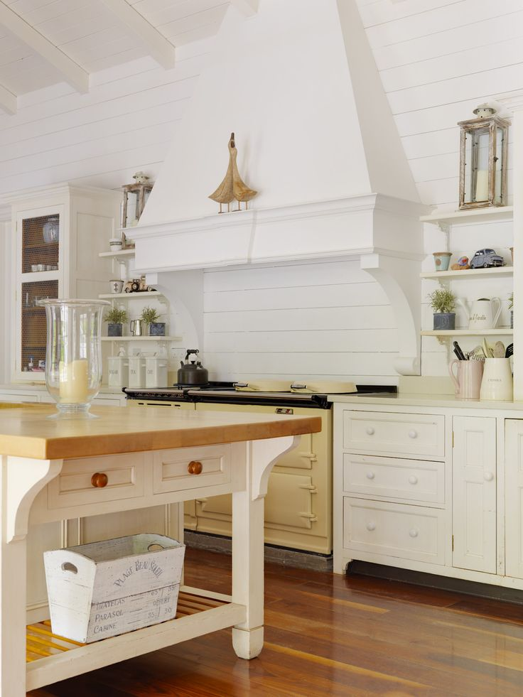 French Country kitchen with shiplap, decorative custom range hood, and white island topped with wood.
