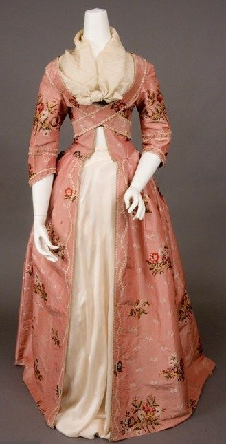 PINK SILK BROCADE ROBE A LA FRANCAISE, 1770-1780. Sack back open gown of rose pink ribbed silk brocaded with scattered multicolored flower sprays and small cream flower sprigs, looped cream silk fringe trim, bodice with pendant self fabric bands to cross-over and pin under arms, center front eyelets forlacing, skirt knife pleated to bodice, interior linen waist tapes and loops for polonaise effect, homespun linen bodice and sleeve linings, hem deeply faced with soft cream China silk. Front