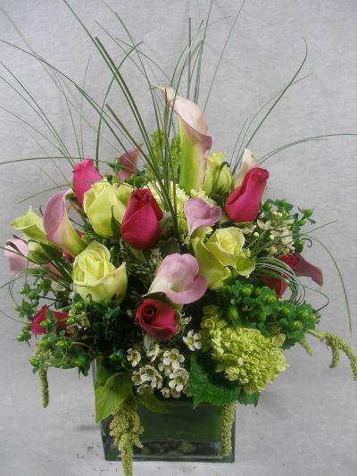 Roses, callas, green hydrangea, waxflower and wispy beargrass.
