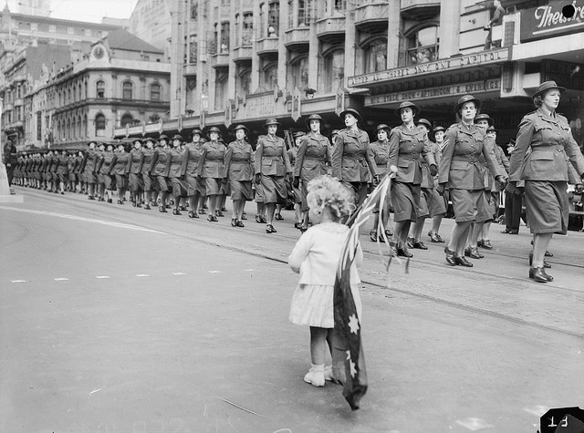 "Members of the Australian Women's Army Service (AWAS) give ""eyes right"" as they pass the saluting base during the Service Womens march through the city. In the foreground a small girl with an Australian flag over her shoulder watches the march."