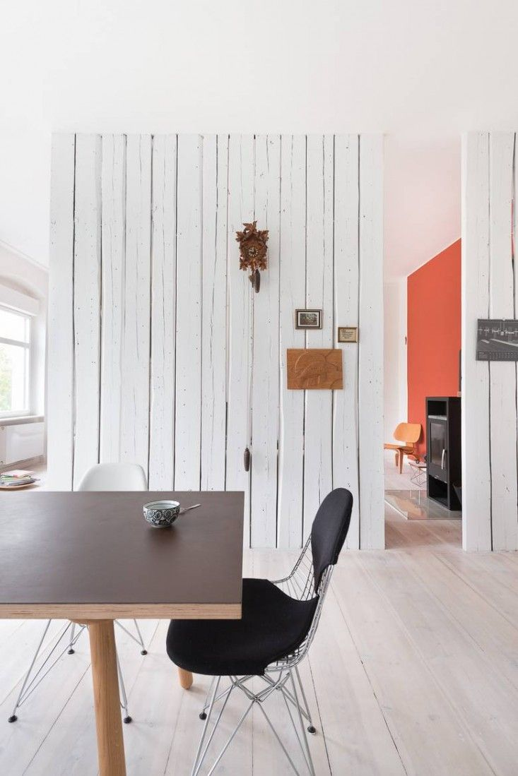 Karhard Architecture and Design, Berlin flat, orange feature wall in living area, stained white floors, Eames bikini chair | Remodelista