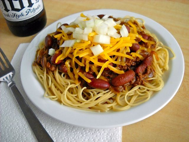 Cincinnati Chili has a uniquely rich red sauce that combines ground beef and chocolate. Topped with diced onion and cheddar cheese it's to die for.