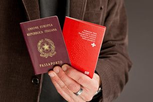 A man holds two passports (Keystone)