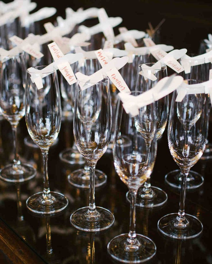 A Spanish-Inspired Wedding in Palm Springs | Martha Stewart Weddings - Calligraphed paper airplanes in champagne flutes served as the escort cards—guests' full names were written on the wings, and the table number was scripted on the tail.