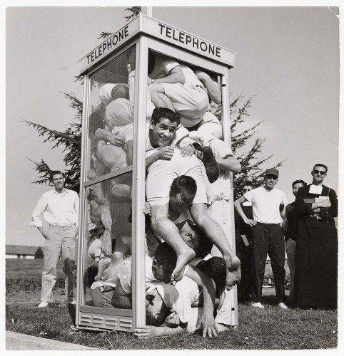 Adolescentes brincando em uma cabine telefônica em 1959.